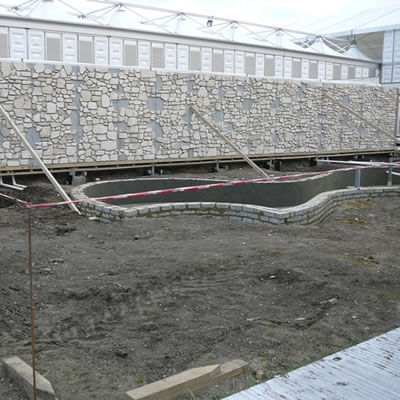 The limestone wall begins to materialize.