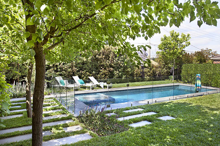 Striking aqua pool tiles make this contemporary pool pop against the vibrant greenery and sleek steppers in Ian Barker Gardens designed Box Hill garden